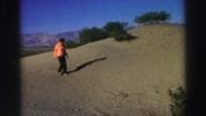 1969: a woman in orange hiking across a sandy dune mountain YOSEMITE, CALIFORNIA Stock Footage
