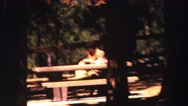 1969: a woman rests sitting on a bench in a pretty wooded rural area YOSEMITE, Stock Footage