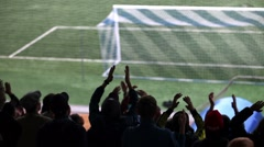 Silhouettes of fans in the background of a football field. Stock Footage