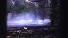 1969: a forest fire along a paved road with a white vehicle driving past. Stock Footage