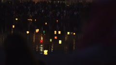 Many people stand along the promenade and look at the water lanterns Stock Footage