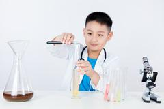 Asian Chinese boy holding test tube for research Stock Photos