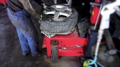 Auto mechanic using special equipment to change tires in garage Stock Footage