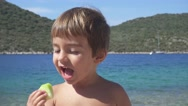 Close up child eating and watching around on the beach Stock Footage