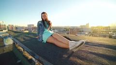 Attractive smiling girl looking at the camera on the roof high above the city Stock Footage