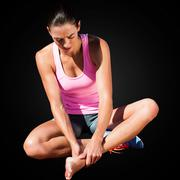 Sportswoman is hurting her foot in a black background Stock Photos