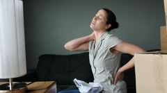 Woman suffers from back pain due to unpacking boxes Stock Footage
