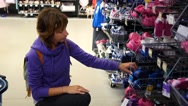 Mom selects item on shelf at child shoes department - a family shopping in store Stock Footage
