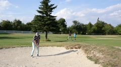 Player man kick the ball from sand bunker on the golf course slow motion Stock Footage