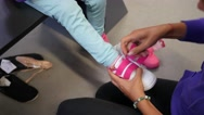 Mom trying on shoes at the foot of the child - a family shopping in a store Stock Footage