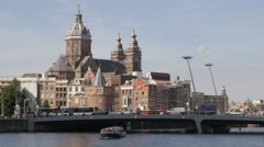 Saint Nicolas Church with canal houses and tour boat,Amsterdam,Netherlands Stock Footage