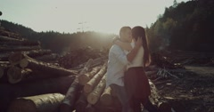 Happy young couple enjoying an intimate moment near logs in forest. Stock Footage