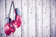 Boxing gloves attached to white background against wooden background Stock Photos