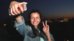 Attractive girl takes a selfie on your smartphone on the roof high above the Stock Footage
