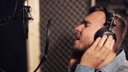 Man with headphones singing at recording studio Stock Footage
