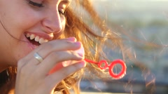 Young attractive girl having fun blowing bubbles on the roof high above the city Stock Footage