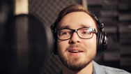 Man with headphones singing at recording studio Stock Footage