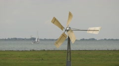Small windmill in field at IJselmeer lake,Noord Holland,Netherlands Stock Footage