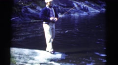 1951: finding the best fishing spot on the rocks at the edge of the lake CANADA Stock Footage