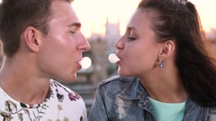 Young loving couple blowing bubblegum candy bubbles on a rooftop in the city at Stock Footage