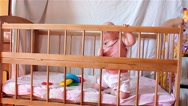 Baby gets to his feet and standing in crib Stock Footage