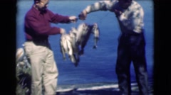 1951: two men showing off lots of big fishes they caught at lake on bright sunny Stock Footage