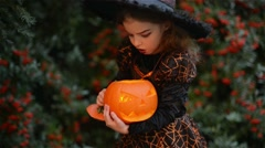 Child little witch on Halloween on a background of autumn leaves, girl holding Stock Footage