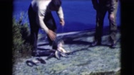 1951: man with huge catch of fish counts his score and shows off to friend Stock Footage