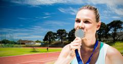 Portrait of sportswoman kissing a medal  against high angle view of track Stock Photos