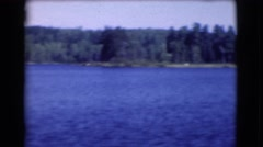 1951: a motorboat travelling across a beautiful blue lake in the wilderness Stock Footage