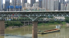 China Chongqing Jialing river road bridge & freight ship Stock Footage