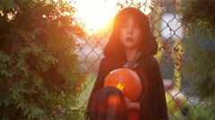 Boy dressed like vampire for Halloween party, dracula holding pumpkin with a Stock Footage