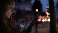 Young woman smiles whilst using a tablet at night in the city, in slow motion Stock Footage