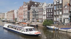 Tour boat with tourists in canal,Amsterdam,Netherlands Stock Footage