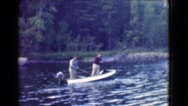 1951: two men fishing in a small boat in a river in the forest CANADA Stock Footage