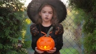 Halloween. Cute girl shows a cheerful witch. She is dressed in a black dress and Stock Footage
