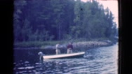 1951: two men fishing in a boat in the lake surrounded by trees CANADA Stock Footage