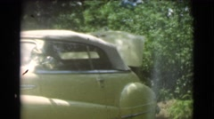 1951: a man unloads the trunk of a cream colored classic automobile  Stock Footage