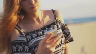 Young girl on the beach with your smartphone. Sunset Stock Footage