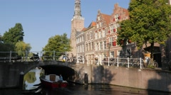 Step houses and church tower along canal with tourist boat,Leiden,Netherlands Stock Footage
