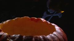 Put bottle beer inside Halloween pumpkin jack o lantern Stock Footage