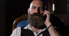4K Portrait of cheerful bearded man talking on cell phone in dimly lit room Stock Footage