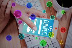 Smartphone apps icons against businesswoman using her smartphone on desk Stock Photos