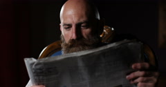 4K Portrait of mature bearded man reading newspaper in dimly lit room Stock Footage