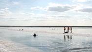 People rest at the exotic salt lake Baskunchak Stock Footage
