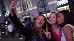 Female friends pull silly faces during a selfie in the city at night Stock Footage