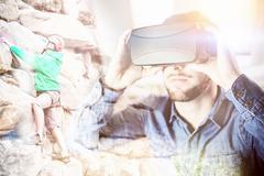 Focused man climbing a large rock face against man wearing virtual glass Stock Photos