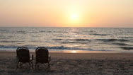 Two chairs near coastline at sunset time Stock Footage