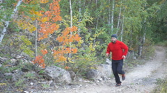 Man running cross country in autumn mountain. Jogging motivation in green par Stock Footage
