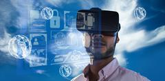 Portrait of businessman holding virtual glasses against blue sky with clouds Stock Photos